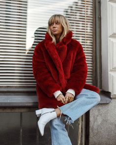 oversized red faux fur coat + light wash flare raw hem jeans + white ankle boots