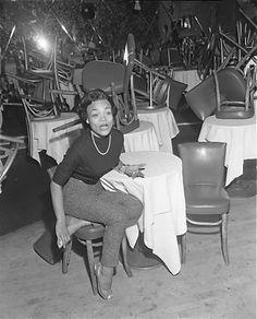 Singer Eartha Kitt, seated in an empty nightclub in Los Angeles, Calif., 1953