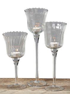 Iată ce surpriză vă aşteaptă în gama noastră de decoraţiuni interioare, setul de pahare pentru lumânări din gama Gloss. Acest produs se comercializează doar la set, conţine 3 pahare cu picior din sticlă transparentă iar dimensiunile acestora sunt cuprinse între 25 şi 35 cm. Vă recomandăm acest set pentru a-l integra în orice decor creând astfel o atmosferă intimă.