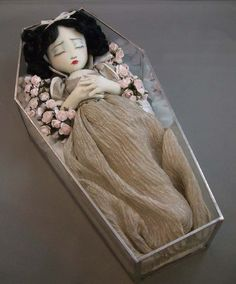 Snow White in her Coffin Doll - After eating a poisoned apple, Snow White falls into a deep sleep that appears as death. The Seven Dwarfs, and all who see her, are so taken by her beauty, even in death, they can't bear to cover her up in a coffin. They build her a glass coffin so all can see her and admire her, even in death.