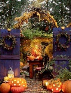 fall garden party setting with a rich mix of textures framed by an iron arch of climbing vines enhanced with a pair of autumn door wreaths on recycled doors painted plum...guests find there way to the enchanting fall scene by the lights of lighted pumpkins and rustic lanterns.  The pumpkins pattern is made easy with the use of a drill and broad bit.-agt.