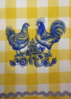A Delft blue hen and rooster machine embroidery design on a kitchen towel.