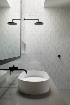 Subtly textured wall, minimal matte black fittings, skylight over shower for natural daylight. MAH Residence, Brighton, Australia, by MIM Design. Photography by Peter Clarke. #modern #bathroom #blackandwhite