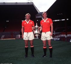 The Greenhoff brothers, Brian and Jimmy, in their Manchester United strip, hold the F.A. Cup which the club won in 1977