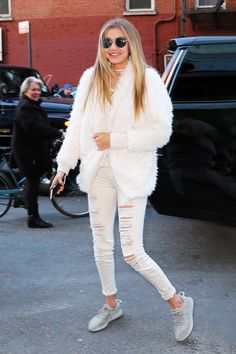 Gigi Hadid does winter whites like a pro in a tee and ripped skinny jeans with a furry coat and gray sneakers