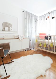 Geometric shape multi-colored mobile and a fuzzy rug baby room