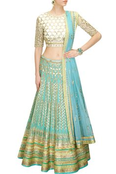 This aqua color bridal lehenga features in georgette fabric paired with white gota patti embroidered choli in net with cut-out detailing at back.