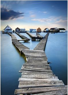 The small lake village of Bokod, Hungary. Along the lake shore, rickety boardwalks lead out over the lake to old fishing cottages that stand on stilts