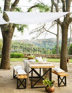 Comedor exterior con toldo tipo vela, mesa de madera y metal, bancos, árboles y vistas al bosque_438317