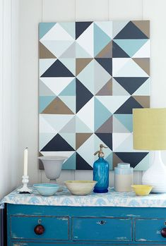 Draw a grid of 10-centimeter squares on a blank canvas, then divide each into six smaller triangles. Mask the edges of all the triangles to be painted in the first color with low-tack tape, then paint. Leave to dry, peel away the tape, and repeat until all triangles are painted.