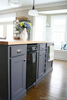 dark gray kitchen island painted with peppercorn from sherwin Williams. Butcher block counter top.
