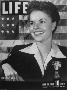 A young woman posing for the cover of LIFE magazine of 06-29-1942, wearing a bell shaped badge indicating she is one of the USO Victory Belles. LIFE