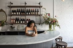 Brunette Wine Bar in the Hudson Valley | Remodelista. Smooth marble meets rough brick, industrial plumbing pipe and wood shelves meet refined mirror, flowers and bent wood stools.