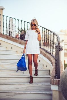 Shop this look on Lookastic:  http://lookastic.com/women/looks/white-shift-dress-black-sunglasses-blue-tote-bag-black-heeled-sandals/10541  — White Shift Dress  — Black Sunglasses  — Blue Leather Tote Bag  — Black Suede Heeled Sandals