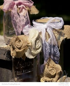 Wedding decorations made with mason jars, lace, and burlap roses.