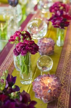 Multiple floral vessels, filled with ranunculus, line this bright green and purple table runner.