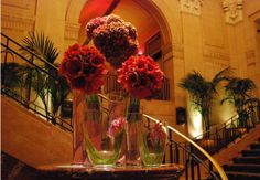 The Peninsula Hotel received a beautiful installation of looping calla lilies, leaning red amaryllis, and leaning red/green hydrangea - By Flowers of the World
