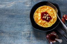 #Pancakes in pan  Close up of american pancakes with pecans and chocolate caramel sauce on vintage cast-iron frying pan over rustic background top view copy space. Delicious dessert for breakfast