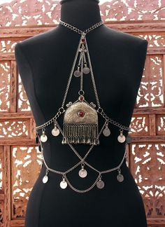 Unique kuchi body drape, accented with lots of dangles, large etched Turkish pendant and authentic kuchi coins. Gorgeous!Easily create an amazing costume- wear this with any halter top , choli, or bra for an instant WOW effect. Will fit most any size due to adjustable chain.