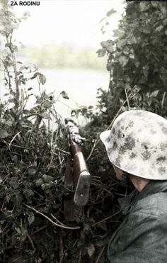 German Luftwaffe Soldier & his K98 rifle on a hedgerow, 1944.