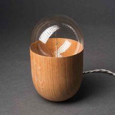 La lampe de table COCO est une création en chêne massif. Sa structure en bois arrondie est recouverte d'un vernis satiné fusionnant avec une ampoule à incandescence diffusant une lumière douce et chaleureuse