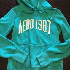 "Aero Pull Over Hoodie Got this in an exchange from a shady seller  Teal with white lettering. Please note print lettering is slightly doscolored, stitch lettering is fine just has a couple ""fuzzies"" Overall in good condition. Comfy and warm, soft cotton. Best fits xs and small Aeropostale Sweaters"