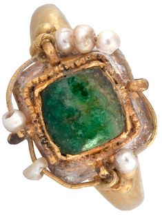 Jewelry Auction - Nov 30th 2016 - Islamic Emerald and Pearl Ring. Circa 6th-7th century AD. The cast gold ring, with a collet of beaded wire, is set with a fine Egyptian emerald. The Romans and Byzantines left the emerald in its natural shape and only polished the surface. The central stone is surrounded by a thin wire threaded through loops and strung with seed pearls. This and more important art for sale on CuratorsEye.com