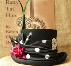 "Ragtime - A vivacious little hat with its striking combination of silky polka dot fabric, tall green pheasant feathers, pink velvet rose and complementary hatpins. Go on….jazz things up with jolly little Ragtime. Ragtime is a black Steampunk top hat with 5"" high crown. It is handmade from 100% wool, lined with satin and finished to a fine heirloom quality."