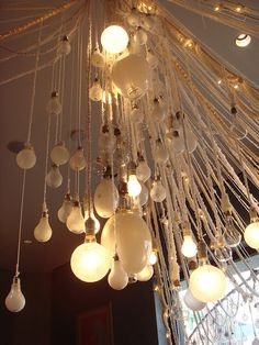 "Sarah Montgomery. hanging ""chandelier"" display with varying sized lightbulbs, braided and crocheted rope/thread/yarn"
