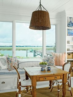 This welcoming breakfast nook has a built-in bench with cabinets underneath for extra storage. Pile it high with pillows for a snug spot to watch the water. The woven hanging lamp and pretty patterns offer texture and interest to this small space.