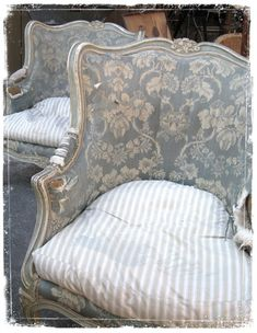 Faded blue toile backs and looks like, ticking pillow seats. Frames painted silver? No. But I wish they were.