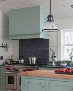 The wall paneling in this picturesque cottage kitchen is original to the farmhouse. Pale blue paint for the range hood and cabinets are a fresh upgrade for the space.