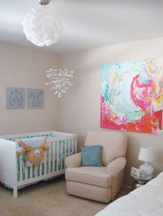 The giant, colorful art piece is what catches my eye in this room.  I like the idea of using a painting in a nursery.  Also, great mobile.