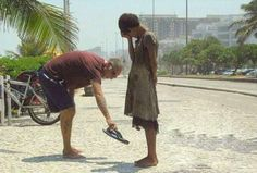 A man gives his shoes to a homeless woman in Rio de Janerio. - Purpleclover.com