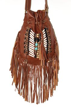 "Boho-chic cross body fringe leather bag with tribal stones. Adjustable shoulder strap and Interior pocket. Handmade in Bali 1"" W x 7"" L x 11"" H (29"" with strap)"