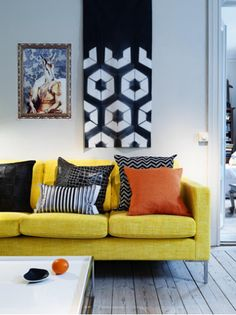 Camilla Julner    yellow sofa, orange and black black zigzag chevron pillow, striped black pillow, plank floors, floor lamp, art and white modern coffee table.