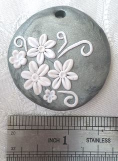 Polymer clay pendant, handmade with applique technique, one of a kind. Silver with white flowers and swirls. By Lis Shteindel.