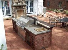 An outdoor kitchen doesn't have to be big, but it should have a bar so the cook doesn't get lonesome.This grill has plenty of work space on either side, plus a bar-height counter in the front. Note the outdoor fireplace at the edge of this brick patio - this home has got a great outdoor entertainment area.