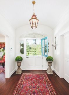 Front hall with a Persian rug, dark floors, light walls, and symmetry.