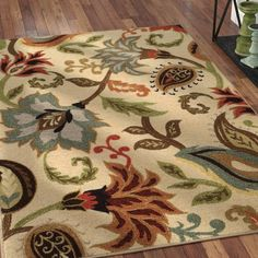Lay a contemporary foundation for your stylish space with this ivory area rug, showcasing an oversized paisley floral motif in muted hues of olive green, blue, and rust. Made in Egypt, this rug is machine woven of stain and fade-resistant nylon in a medium 0.24'' pile—perfect for laying out in high-traffic areas and places prone to stains and spills. Available in a curated selection of sizes to best suit your space, this rug features a non-slip rubber backing to prevent shifting and sliding.