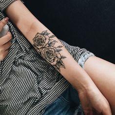 Tatuaggi donna, idea per un tattoo con due rose di colore nero da fare sul braccio