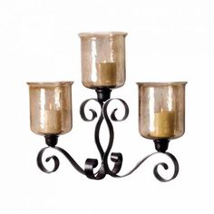 Hammered Brown Lustre Glass Hurricane Candelabra  Three Light Hammered Glass Hurricane Candelabra with Scrollwork Iron Base Collection: Cheyenne Finish: Rustic, Hammered Brown Lustre Material: Glass, Metal Overall Dimensions in Inches: Height: 24 Width: 28.8 Length: 11.6 CODE: ELK-561535