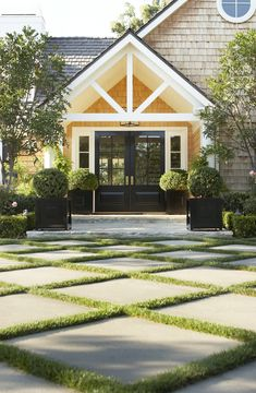 This expansive front yard has five gardens, each with its own look. For this area, Shrader interspersed concrete squares with grass and planted a…