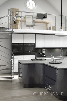 Gloss handleless kitchen combining two colours - white and anthracite. A large, curving island design is the centrepiece of this modern apartment kitchen layout. For more information, please see http://www.chippendalekitchens.co.uk/kitchens/solo-gloss-anthracite