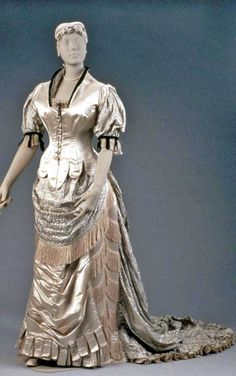 Evening dress, Worth, ca. 1880-85. Pale blue & figured (narrow vertical stripes of coral-like motifs in darker blue) satin; bodice ending in tabs at front lower edge, pleated peplum in back, short full sleeves of figured satin, wired rolled collar of black velvet. Skirt has draped front panel ending in tabs with swags of grayish white silk & clear glass bead fringe. Draped apron front, sides, & back of figured satin, most of fullness of skirt in back. Museum of Fine Arts, Boston