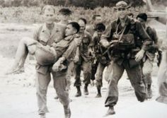 Sgt. Robert L. Howard carries a North Vietnamese Army POW to received medical treatment. Howard served five tours in Vietnam, commissioned as an officer in 1969, and earned the Medal of Honor. He retired as a colonel and passed away in December 2009. (Source: army.mil)