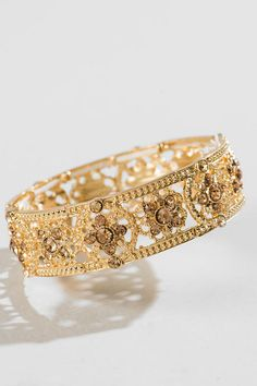 """The Nona Stretch Bracelet is a gorgeous addition to your jewelry collection. This golden bracelet features a floral filigree design accented with gold crystals. Wear this with your party dress & gold heels for a complete look.<br /> <br /> - 2.25"""" diameter<br /> - Lead & nickel free<br /> - Imported"""
