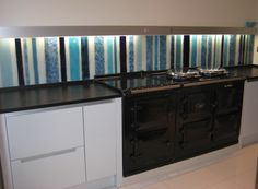This bespoke blue stripe fused glass kitchen splashback was commissioned by our client in their choice of colours. Halogen downlighters enhance the glass colours which are complemented by the white gloss kitchen and black Aga.