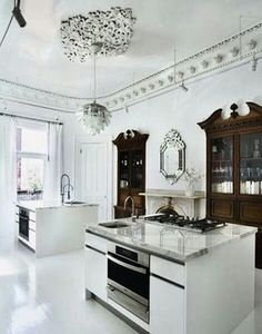 White kitchen mixing modern lines and lighting with heritage pieces
