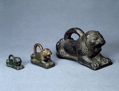 Lion shaped measuring weight; copper alloy; inscribed; a cross perhaps intended to indicate two-thirds is incised on the flank of the lion. 1848,1104.78, AN45417001